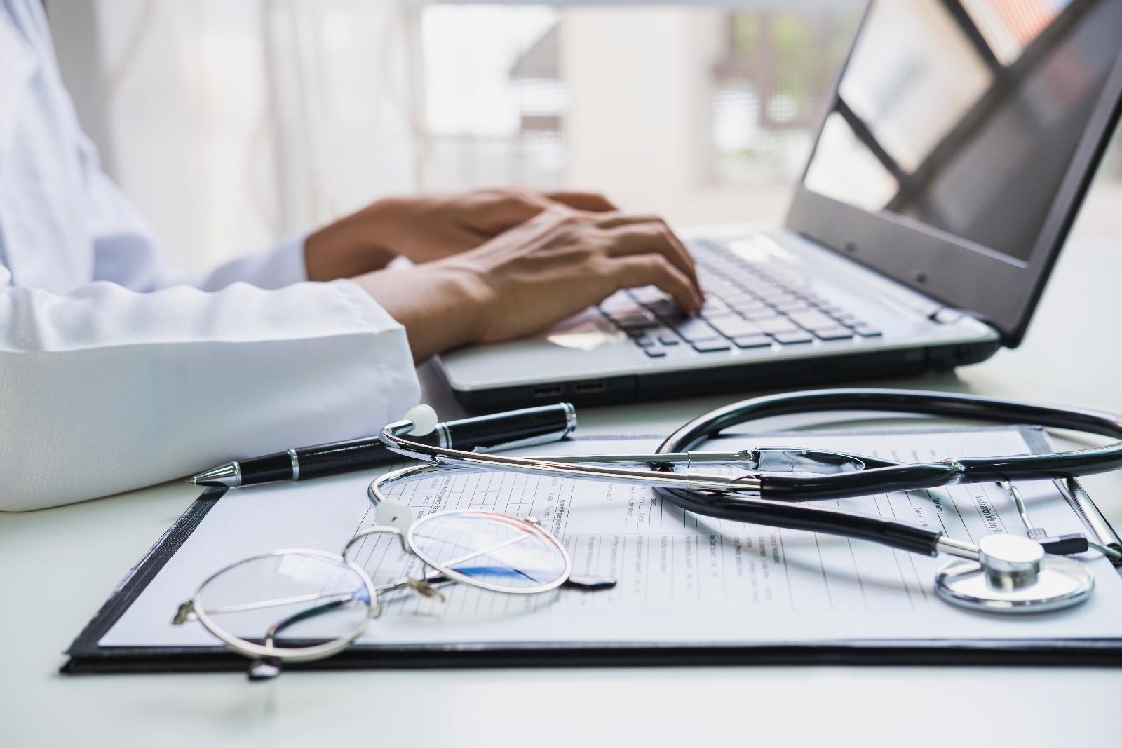 Lääkäri kirjoittaa tietokoneella